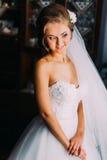 Schöne blonde Braut im eleganten weißen Kleid, das nahe Fenster aufwirft Stockbilder
