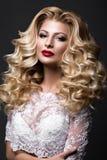 Schöne blonde Braut im Hochzeitsbild mit Locken, rote Lippen Schönes lächelndes Mädchen Stockfotografie