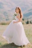Schöne blonde Braut im Hochzeitskleid läuft über das Feld in Richtung zu den Bergen Stockbild