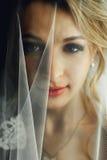 Schöne blonde Braut im Make-up und Schleier ein in den weißen Kleid-clos Stockfoto