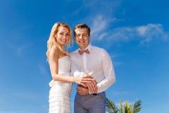 Schöne blonde Braut im weißem Hochzeitskleid und -bräutigam übergibt SH lizenzfreie stockfotografie