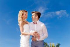 Schöne blonde Braut im weißem Hochzeitskleid und -bräutigam übergibt SH stockfotos