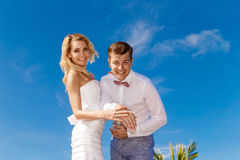 Schöne blonde Braut im weißem Hochzeitskleid und -bräutigam übergibt SH Stockfotografie