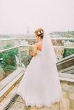 Schöne blonde Braut im weißen Hochzeitskleid, das unten dem Balkon des Luxushotelraumes betrachtet Stockbilder