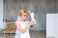 Schöne blonde Braut im weißen Hochzeitskleid mit Frisur und hellem Make-up auf dem Haupthintergrund, der im Spiegel schaut Stockfotos
