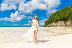 Schöne blonde Braut im weißen Hochzeitskleid mit großem langem Weiß Stockfotos