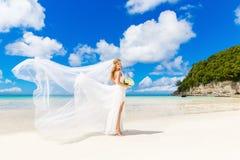 Schöne blonde Braut im weißen Hochzeitskleid mit großem langem Weiß Lizenzfreie Stockfotografie