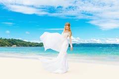 Schöne blonde Braut im weißen Hochzeitskleid mit großem langem Zug Stockbilder