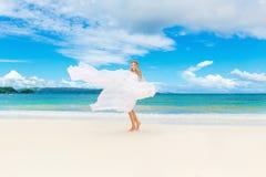 Schöne blonde Braut im weißen Hochzeitskleid mit großem langem Zug Stockfotografie