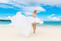 Schöne blonde Braut im weißen Hochzeitskleid mit großem langem Zug Lizenzfreie Stockfotos