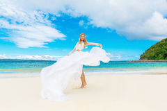 Schöne blonde Braut im weißen Hochzeitskleid mit großem langem Zug Stockbild