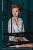 Schöne blonde Braut im weißen Negligé, das auf der schwarzen Schmiedeeisentreppe sitzt Stockbilder