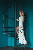 Schöne blonde Braut im weißen Negligé gehend herauf schwarzes Schmiedeeisentreppenhaus Stockfotos