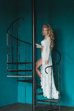 Schöne blonde Braut im weißen Negligé gehend herauf schwarzes Schmiedeeisentreppenhaus Stockfotografie