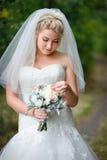 Schöne blonde Braut mit Blumenstrauß Stockfotografie