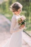 Schöne blonde Braut mit Blumenstrauß des Frühlinges blüht im Freien Stockbild