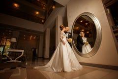 Schöne blonde Braut mit Bräutigam am Spiegel Lizenzfreie Stockbilder