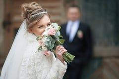 Schöne blonde Braut mit dem aufwerfenden Hochzeitsblumenstrauß, Nahaufnahme Stockbild