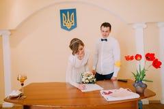 Schöne blonde Braut mit Heirat-Hochzeitszertifikat des Brautblumenstraußes unterzeichnendem am Register Lizenzfreie Stockfotos