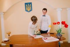 Schöne blonde Braut mit Heirat-Hochzeitszertifikat des Brautblumenstraußes unterzeichnendem am Register Stockbilder