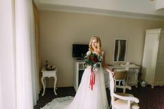 Schöne blonde Braut mit Hochzeitsblumenstrauß in den luxuriösen Wohnungen Stockfoto