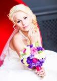 Schöne blonde Braut mit Hochzeitsblumenstrauß von Blumen Lizenzfreie Stockfotografie