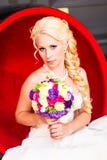 Schöne blonde Braut mit Hochzeitsblumenstrauß von Blumen Lizenzfreie Stockfotos