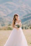 Schöne blonde Braut mit Hochzeitsblumenstrauß von Blumen draußen auf Gebirgshintergrund Stockbild
