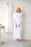 Schöne blonde Braut nahe weißer Backsteinmauer Stockbild