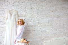 Schöne blonde Braut nahe weißer Backsteinmauer Lizenzfreie Stockbilder