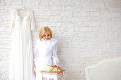 Schöne blonde Braut nahe weißer Backsteinmauer Lizenzfreie Stockfotografie