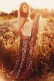 Schöne blonde Dame auf dem Blumengebiet bei Sonnenuntergang Stockfotografie