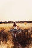 Schöne blonde Dame auf dem Blumengebiet bei Sonnenuntergang Lizenzfreies Stockbild
