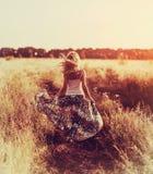 Schöne blonde Dame auf dem Blumengebiet bei Sonnenuntergang Stockfoto