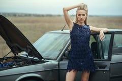 Schöne blonde Dame in der luxuriösen dunkelblauen Paillettequasten-Abendkleiderstellung an ihrem alten Auto mit offener Haube stockfotos