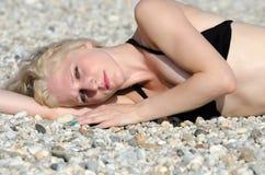 Schöne blonde Dame, die auf den Kieseln liegt, setzen auf den Strand Stockfotos