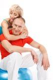 Schöne blonde Dame, die gealterten Mann umarmt Stockbilder