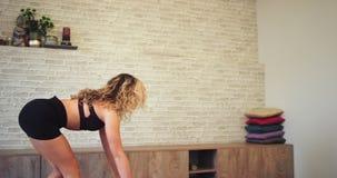 Schöne blonde Dame, die ihren Platz in einem Yogastudio sich hinsetzt im Boden in ihrer Sportmatte und zu fertig werden geht