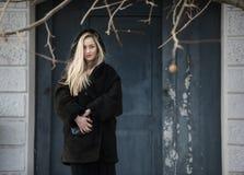 Schöne blonde Dame gegen blaue alte Tür Stockfotografie