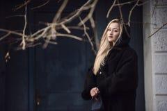 Schöne blonde Dame gegen blaue alte Tür Stockfoto