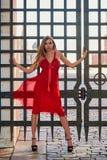 Schöne blonde Dame im roten Kleid auf Rotem Platz Stockfoto