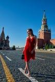 Schöne blonde Dame im roten Kleid auf Rotem Platz Lizenzfreies Stockfoto