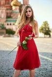 Schöne blonde Dame im roten Kleid auf Rotem Platz Lizenzfreie Stockfotos