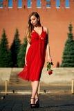 Schöne blonde Dame im roten Kleid auf Rotem Platz Stockbild