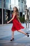 Schöne blonde Dame im roten Kleid auf weißem Quadrat Stockfoto