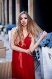 Schöne blonde Dame im roten Kleid auf weißem Quadrat Stockfotografie