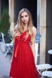 Schöne blonde Dame im roten Kleid auf weißem Quadrat Lizenzfreies Stockbild