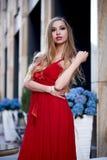 Schöne blonde Dame im roten Kleid auf weißem Quadrat Stockfotos
