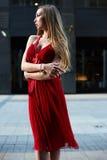 Schöne blonde Dame im roten Kleid auf weißem Quadrat Lizenzfreies Stockfoto