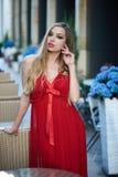 Schöne blonde Dame im roten Kleid auf weißem Quadrat Stockbild